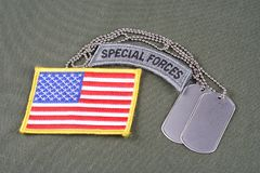 US ARMY special forces tab with dog tag and flag patch on olive green uniform. Background Stock Image