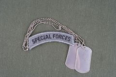 US ARMY special forces tab with dog tag on olive green uniform. Background Royalty Free Stock Photos