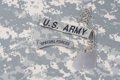 US ARMY special forces tab with dog tags on camouflage uniform. Background Royalty Free Stock Photos