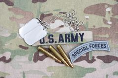 US ARMY special forces tab, flag patch, with dog tag and 5.56 mm rounds on camouflage uniform. US ARMY special forces tab, flag patch,  with dog tag and 5.56 mm Stock Images