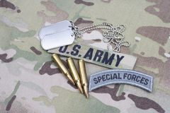 US ARMY special forces tab, flag patch, with dog tag and 5.56 mm rounds on uniform. US ARMY special forces tab, flag patch, with dog tag and 5.56 mm rounds on Stock Photos