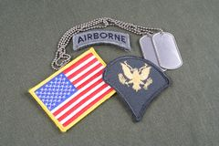 US ARMY Specialist rank patch, airborne tab, flag patch and dog tag on olive green uniform. Background Royalty Free Stock Image