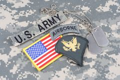 US ARMY Specialist rank patch, airborne tab, flag patch,  with dog tags on camouflage uniform. Background Royalty Free Stock Photos