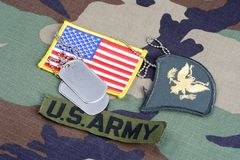 US ARMY Specialist rank patch, branch tape, flag patch and dog tags on woodland camouflage uniform. Background Stock Photos