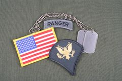 US ARMY Specialist rank patch, ranger tab, flag patch and dog tag on olive green uniform Royalty Free Stock Images