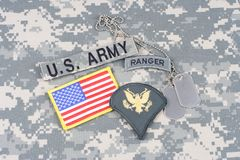 US ARMY Specialist rank patch, ranger tab, flag patch,  with dog tag on camouflage uniform Stock Photos