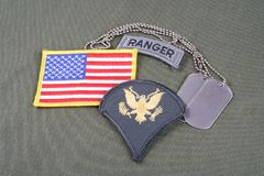 US ARMY Specialist rank patch, ranger tab, flag patch and dog tag on olive green uniform Stock Photos