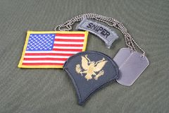 US ARMY Specialist rank patch, sniper tab, flag patch and dog tag on olive green uniform. Background Stock Photo