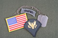 US ARMY Specialist rank patch, sniper tab, flag patch and dog tag on olive green uniform. Background Royalty Free Stock Photography