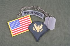 US ARMY Specialist rank patch, special forces tab, flag patch and dog tag on olive green uniform. Background Royalty Free Stock Photography