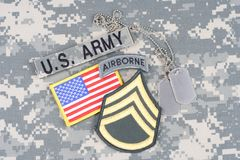 US ARMY Staff Sergeant rank patch, airborne tab, flag patch, with dog tag on camouflage uniform. Background royalty free stock photos