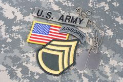 US ARMY Staff Sergeant rank patch, airborne tab, flag patch, with dog tag on camouflage uniform. Background stock images