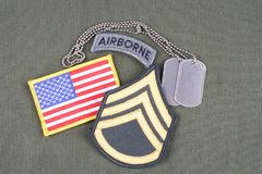 US ARMY Staff Sergeant rank patch, airborne tab, flag patch and dog tag on olive green uniform. Background royalty free stock images