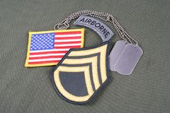 US ARMY Staff Sergeant rank patch, airborne tab, flag patch and dog tag on olive green uniform. Background stock photo