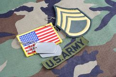 US ARMY Staff Sergeant rank patch, branch tape, flag patch and dog tags on woodland camouflage unif. Orm stock photo