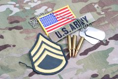 US ARMY Staff Sergeant rank patch, flag patch, with dog tag and 5.56 mm rounds on uniform. US ARMY Staff Sergeant rank patch, flag patch, with dog tag and 5.56 stock photos