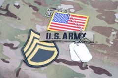 US ARMY Staff Sergeant rank patch, flag patch, with dog tag on camouflage uniform. Background royalty free stock photos