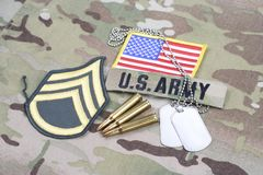 US ARMY Staff Sergeant rank patch, flag patch, with dog tag with 5.56 mm rounds on camouflage u. Niform stock images