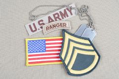 US ARMY Staff Sergeant rank patch, ranger tab, flag patch and dog tag. Background royalty free stock photography