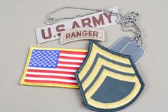 US ARMY Staff Sergeant rank patch, ranger tab, flag patch and dog tag. Background stock image