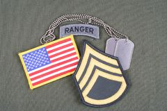 US ARMY Staff Sergeant rank patch, ranger tab, flag patch and dog tag on olive green uniform Royalty Free Stock Photo