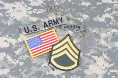 US ARMY Staff Sergeant rank patch, ranger tab, flag patch,  with dog tag on camouflage uniform Stock Photography