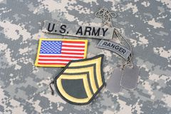 US ARMY Staff Sergeant rank patch, ranger tab, flag patch,  with dog tag on camouflage uniform Royalty Free Stock Photography