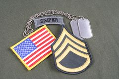 US ARMY Staff Sergeant rank patch, sniper tab, flag patch and dog tag on olive green uniform. Background royalty free stock photo