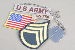 US ARMY Staff Sergeant rank patch, sniper tab, flag patch and dog tag. Background royalty free stock photo