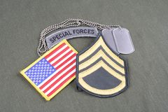 US ARMY Staff Sergeant rank patch, special forces tab, flag patch and dog tag on olive green unif. Orm stock photography