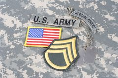US ARMY Staff Sergeant rank patch, special forces tab, flag patch, with dog tag on camouflage un. Iform background royalty free stock photos
