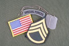 US ARMY Staff Sergeant rank patch, special forces tab, flag patch and dog tag on olive green uni. Form background stock photo