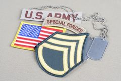US ARMY Staff Sergeant rank patch, special forces tab, flag patch and dog tag. Background royalty free stock images