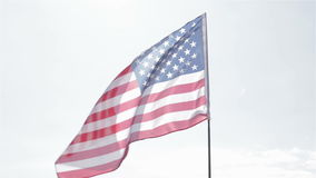 US Banner in the Sky. Flag of the USA against a blue sky stock footage