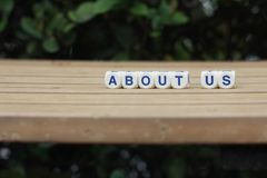 About us. Biography cube letters on horizontal wood plank leaf background Stock Images