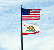 US and California flags. On the same pole, wind blowing hard Royalty Free Stock Photo