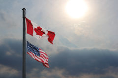 US and Canada Current Affairs. Two flags flying together showing the spirit of cooperation