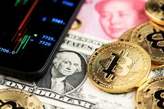 Bitcoin  Cryptocurrency coins on US Dollar and Yuan China currency banknotes next to mobile phone showing candlestick chart. stock images
