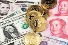 Bitcoin Cryptocurrency coins and US Dollar and Yuan China currency banknotes.