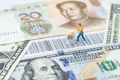 US and China trade, import or export retail ecommerce shopping c. Oncept, miniature people figurine with grocery in the shopping cart rally on the bar code with stock photo