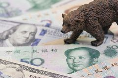 US and China trade war and tariff impact to bear market, price drop in stock concept, bear figure walking on pile of United States. And Chinese banknotes, world royalty free stock photo