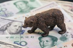 US and China trade war and tariff impact to bear market, price drop in stock concept, bear figure walking on pile of United States. And Chinese banknotes, world royalty free stock images
