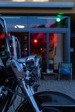 Us chopper motorbike in front of bistro and pub neon lights at e. Bistro and pub neon lights at evening in city mall of south germany metropole with motorbike stock photo