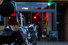 Us chopper motorbike in front of bistro and pub neon lights at e. Bistro and pub neon lights at evening in city mall of south germany metropole with motorbike royalty free stock image