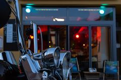 Us chopper motorbike in front of bistro and pub neon lights at e. Bistro and pub neon lights at evening in city mall of south germany metropole with motorbike stock photos