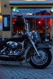 Us chopper motorbike in front of bistro and pub neon lights at e. Bistro and pub neon lights at evening in city mall of south germany metropole with motorbike royalty free stock photo