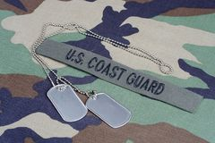 US COAST GUARD bbranch tape and dog tags on woodland camouflage uniform Royalty Free Stock Photos
