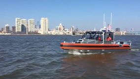 US Coast Guard boat drives along city coast. A US Coast Guard boat drives along a coast. In the background is a US city stock video