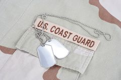 US COAST GUARD branch tape with d. Og tags on desert camouflage uniform background royalty free stock photos