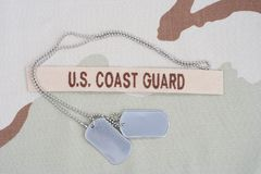 US COAST GUARD branch tape with dog tags on desert camouflage uniform Stock Image